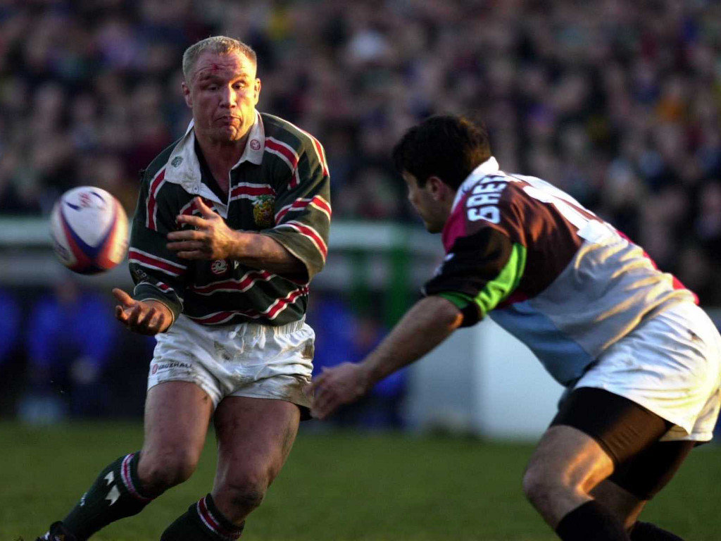 Neil Back of Leicester gets his pass away before the tackle of Nick Greenstock of Harlequins